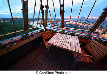Wooden chairs and table at terrace in restaurant; panorama of evening Moscow