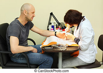 Woman dressed in white coat manicure man by special tongs in...