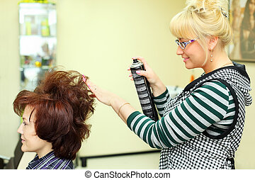 Hairdresser makes hair styling for woman by hair spray in beauty salon; focus on hairdo