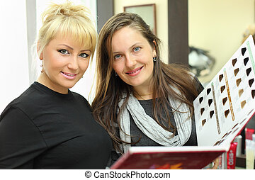 Smiling client and hairdresser with catalog of hair colors...