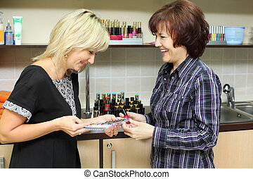 Woman shows samples for manicure nail to customer in beauty salon