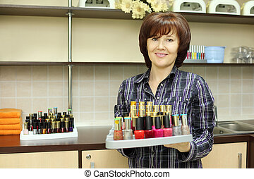 Smiling woman holds colored nail polish on stand in beauty salon