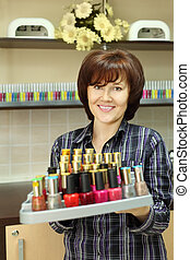 Smiling woman holds colored nail polish on stand in beauty salon; vertical view