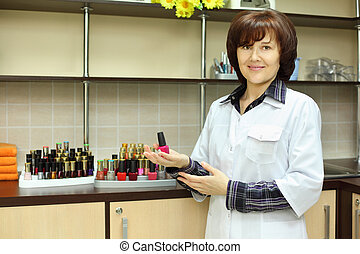 Smiling woman dressed in white robe hold pink nail polish in beauty salon; lot of nail polish on shelf
