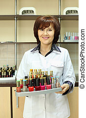 Smiling woman dressed in white robe holds colored nail polish on stand in beauty salon; vertical view