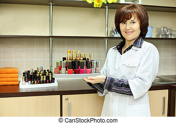 Smiling woman dressed in white robe holds colored nail polish on stand in beauty salon