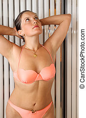 Beautiful woman dressed in orange swimsuit stands in...