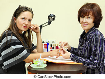 Manicurist makes manicure by nailfile for woman in beauty salon; two woman look at camera