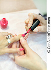 Female hands manicure woman by pink nail polish in beauty...