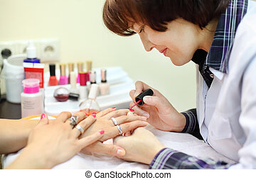 manicurist makes manicure for woman by pink nail polish in beauty salon; focus on brush
