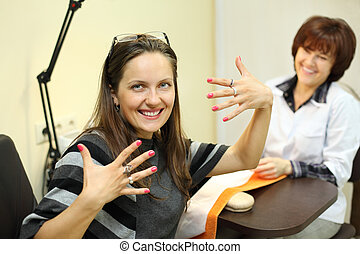 manicurist made manicure for woman in beauty salon; happy customer shows her nails; focus on client