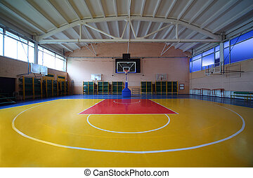 School gym hall with red-yellow floor and basket lighted by...