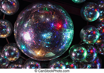 Beautiful shiny balls with colorful lights on ceiling in night club