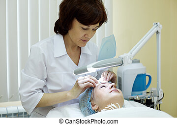 Beautician in beauty salon cleans facial skin of woman.