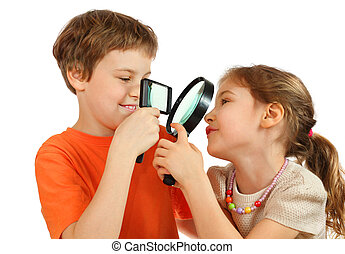 Brother and sister looking at each other through magnifying glasses isolated on white background; focus on lenses