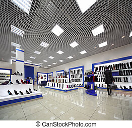 Inside spacious lighting shoes shop with models on white...