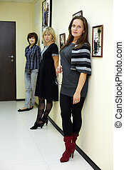 Three women stand in the hallway, leaning their backs to the wall with photos made by Pavel Losevsky and look in the same direction