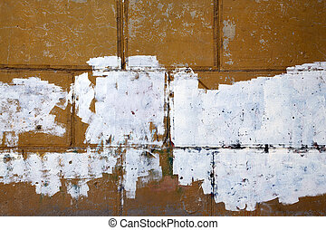 Fragment of the old peeling brown wall with traces of white putty
