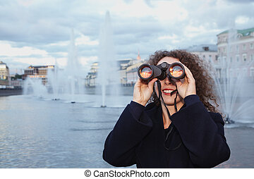 Young woman looks through binoculars at the sunset, standing on the background of fountains