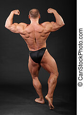 Undressed bronzed bodybuilder shows the muscles of hands, legs and back
