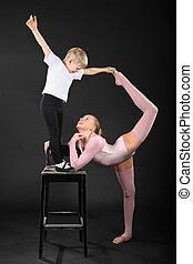 Girl and little boy gymnast took graceful pose at bark chair...