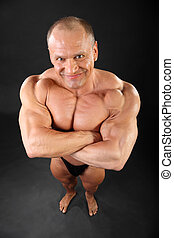 Undressed barefoot tanned bodybuilder smiles inside black...