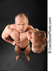 Undressed formidable tanned bodybuilder punches to camera...