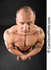 Undressed formidable tanned bodybuilder looks at camera...
