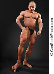 Undressed tanned bodybuilder touches floor by toe inside...