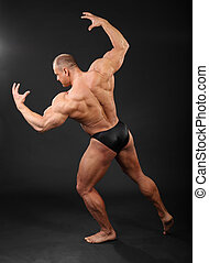 Undressed tanned bodybuilder shows muscles of arms and back in black studio