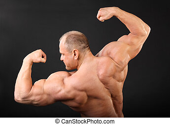 Undressed tanned bodybuilder shows muscles of arms and back...