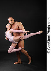 Undressed sunburnt bodybuilder holds graceful girl in black studio