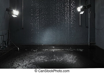 Rain in studio with black walls, lighting system for high-quality photography