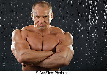 Thoughtful tanned undressed bodybuilder stands in rain inside studio