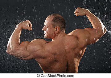 Undressed bodybuilder stands in rain back to camera and...