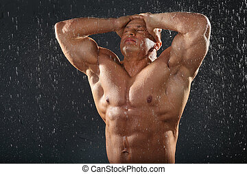 Undressed tanned bodybuilder in rain holds his head by hands...