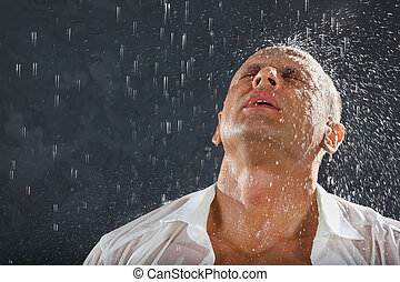 Man wearing white wet shirt stands in rain and drops fall on...