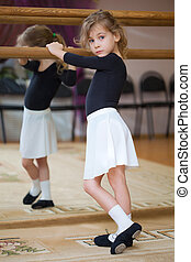 Little girl poses at ballet barre. Reflection in mirror.