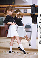 Girl at ballet barre. Ballet pas. Right profile. Reflection...