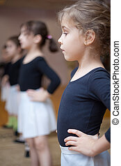 Young ballerinas stand in first position. Focus on first...