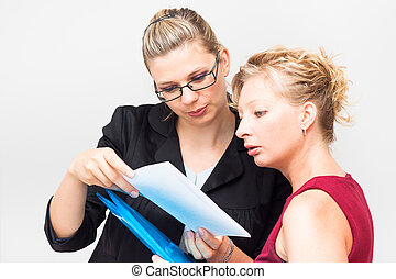 Serious businesswomen looking at document