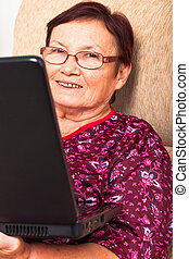 Happy elderly woman with laptop - Close up of happy smiling...