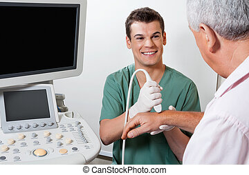 Happy Technician Scanning Male Patient's Hand - Young male...