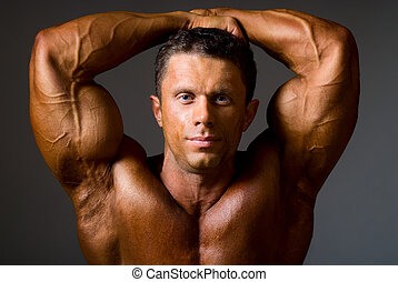 Bodybuilder showing his muscles, closeup.
