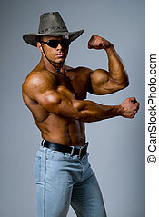 Handsome muscular man in a hat showing his muscles on a gray...