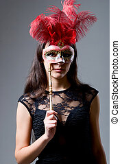 Portrait of a girl in a mask with red feathers