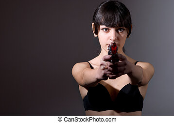 Young woman holding a gun on dark background