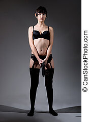 Full-length portrait of a girl with a gun in his underwear