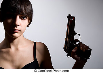 Sexy woman holding gun on gray.