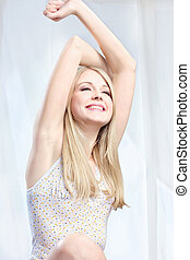 woman stretching arms above head - Young pretty blond woman...